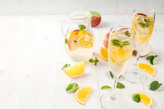 White autumn sangria. Drinks and cocktails. White autumn sangria with apples, orange, mint and white wine. In glasses for champagne, in a pitcher, on a white royalty free stock image