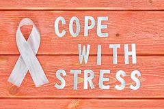 White awareness ribbon and inscription of iron letters: cope with stress lying on wooden textured background color of season 2019. White awareness ribbon and the stock photos