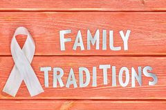 White awareness ribbon and inscription of iron letters: family traditions, lying on wooden textured background color of season. White awareness ribbon and the royalty free stock image