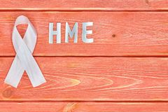 White awareness ribbon and inscription of iron letters: hme, lying on wooden textured background color of season 2019. White awareness ribbon and the inscription stock images