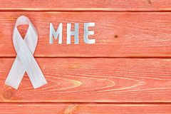 White awareness ribbon and inscription of iron letters: mhe, lying on wooden textured background color of season 2019. White awareness ribbon and the inscription royalty free stock images