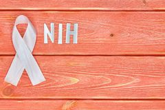 White awareness ribbon and inscription of iron letters: nih, lying on wooden textured background color of season 2019. White awareness ribbon and the inscription royalty free stock photography