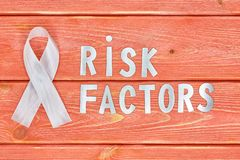 White awareness ribbon and inscription of iron letters: risk factors, lying on wooden textured background color of season 2019. White awareness ribbon and the royalty free stock photo