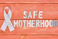 White awareness ribbon and inscription of iron letters: safe motherhood, lying on wooden textured background color of season 2019. White awareness ribbon and the stock image