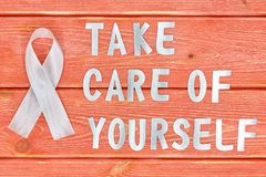 White awareness ribbon and inscription of iron letters: take care of yourself, lying on wooden textured background color of season. White awareness ribbon and stock photography