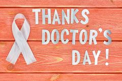 White awareness ribbon and inscription of iron letters: thanks doctors day lying on wooden textured background color of season. White awareness ribbon and the royalty free stock images