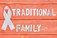 White awareness ribbon and inscription of iron letters: traditional family, lying on wooden textured background color of season. White awareness ribbon and the stock photo