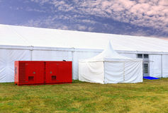 White awning and utility plugin. White tent and technical support unit  at the exhibition camp Royalty Free Stock Image