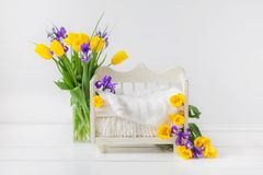 White baby bed for a newborn child on a white background, decorated with yellow tulips and purple irises stock photography