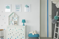 White baby bedroom with dresser. Pouf and wall posters Stock Photos