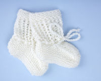 White Baby Booties on Blue Stock Photo