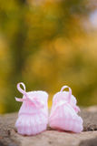 White Baby booties on a green natural background. In autumn Royalty Free Stock Photos