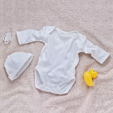 White baby clothes and pacifier on soft carpet Royalty Free Stock Photography
