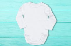 White baby mock up jumpsuit on blue wooden background. Baby bodysuit mockup and template blank copy space. Top Front view.