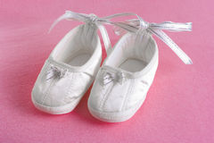 White baby's bootees or shoes on pink sheet Royalty Free Stock Photography