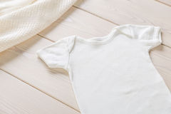 White baby shirt. On wooden desktop. Mock up Stock Photography