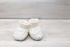 White baby shoes with blue little stars on a wooden background. White baby shoes with blue young stars Stock Image