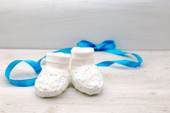 White baby shoes with blue young stars and blue ribbon on the ba Royalty Free Stock Photos