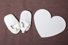 White baby shoes and plastic heart over brown Royalty Free Stock Photography