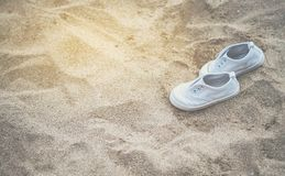 White baby sneakers On the sandy beach stock image