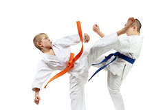 On a white background athletes are beating to meet each other the blows legs Royalty Free Stock Images