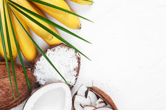 White background with bananas, coconuts and leaf. White background with bananas, coconuts and palm leaf Royalty Free Stock Photos