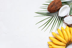 White background with bananas, coconuts and leaf. White background with bananas, coconuts and palm leaf Royalty Free Stock Photo