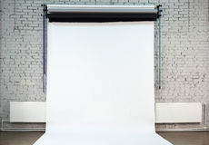 White background on brick wall inside studio Stock Image