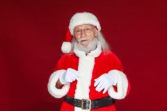 Christmas. Serious Santa Claus in white gloves adjusts her glasses and stares into the camera. on red. White background. Christmas. Santa Claus Celebration stock photo