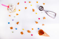 White Background with colorful candies, pieces of waffles, ice cream and empty ice cream cone. Place for lettering. Top view, flat Stock Images