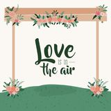 White background colorful scene with grass decorative frame in wooden poles with floral ornaments and text with love is. In the air vector illustration Stock Photos
