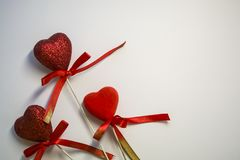 White background. Congratulation. St. Valentine`s Day. Red hearts in spangles and with bows. A decor for the house. Love. White background. Congratulation stock photo