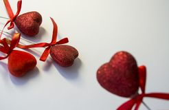 White background. Congratulation. St. Valentine`s Day. Red hearts in spangles and with bows. A decor for the house. Love. White background. Congratulation stock photos