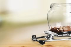 Money Jar with coins and stethoscope, close-up royalty free stock image