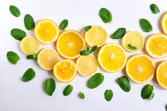 White background with lemon, orange slices and mint. Concept with fresh fruit. Lemon, Orange, Mint. View from above. royalty free stock photo