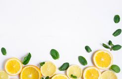 White background with lemon, orange slices and mint. Concept with fresh fruit. Lemon, Orange, Mint. View from above stock images