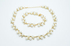 On a white background lies a pearl necklace on the neck and bracelet Royalty Free Stock Photo