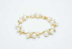 On a white background lies a pearl necklace on the neck and bracelet Stock Image