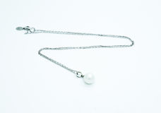 On a white background lies a pearl necklace on the neck and bracelet Royalty Free Stock Photography