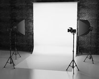 White background lit with Studio equipment against a brick wall. Royalty Free Stock Image
