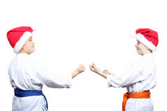 On a white background little athletes in caps of Santa Claus are standing in rack of karate Royalty Free Stock Photography