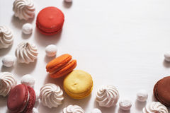White background with meringue, macaroons and cranberries in sugar. White background with a scattering of meringues, macaroons and cranberry in sugar Stock Photography