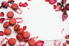 White background with petals of red roses, macaroons and caramel sticks stock images
