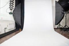 White background in photo studio. Empty photo studio interior with white background and lighting equipment royalty free stock photos