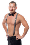 On a white background portrait of a man with a naked torso. In suspenders royalty free stock photography