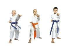On a white background three athletes beat blow gyaku-tsuki Stock Photos