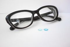 Rigid contact lenses and glasses. On a white background two blue lenses for the eyes. Behind them is a dark female frame with thick glasses. Macro photography Stock Images