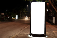 White  backlit ad space advertisement billboard outdoor. At night next to a road Royalty Free Stock Photo