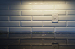 White Backsplash with Light. White Kitchen backsplash with a white outlet on the right side with granite countertop. Light shining down from the top stock images