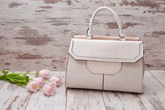 White bag with a handle on a wooden background, pink tulips. Fashionable concept Royalty Free Stock Photo